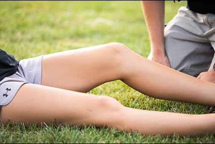 girl on field with leg injury